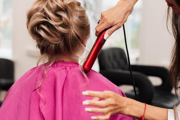 Une fille-coiffeuse fait les cheveux d'un client pour une fête à l'aide d'un fer à lisser.