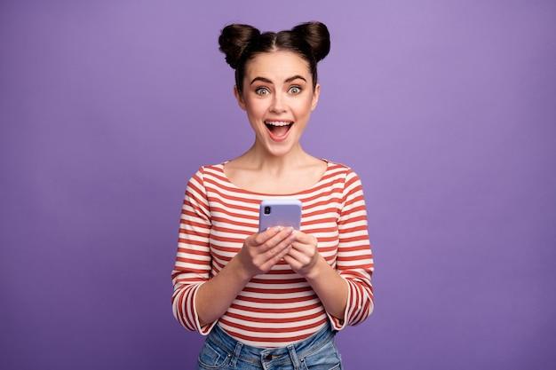 Fille avec une coiffure à la mode à l'aide de téléphone isolé sur violet