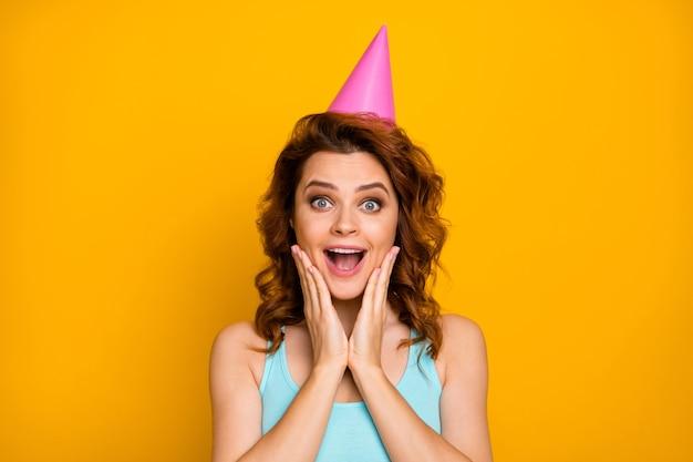 Fille avec une coiffure à la mode et un chapeau de fête isolé sur orange