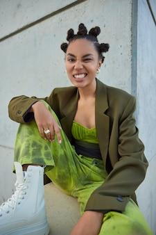 Une fille avec une coiffure à la mode vêtue de vêtements élégants, des bottes blanches se sent des poses cool contre un mur gris appartient à la sous-culture des jeunes