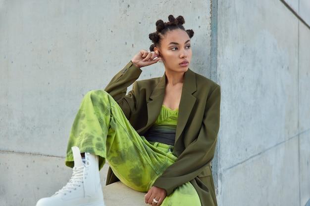 Fille avec une coiffure à la mode vêtue de vêtements verts regarde loin pose contre un mur gris urbain considère quelque chose