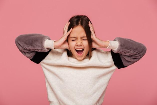 Fille en colère criant et tenant la tête avec les mains isolées