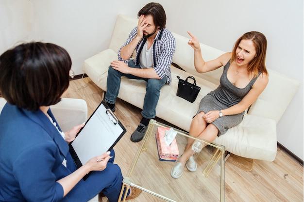 Fille en colère est assise sur le canapé avec son mari. elle regarde un thérapeute mais crie et pointe l'homme.