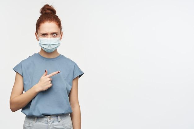 Fille en colère et mécontente aux cheveux roux rassemblés en un chignon. porter un t-shirt bleu et un masque protecteur. pointant vers la droite à l'espace de copie, isolé sur un mur blanc