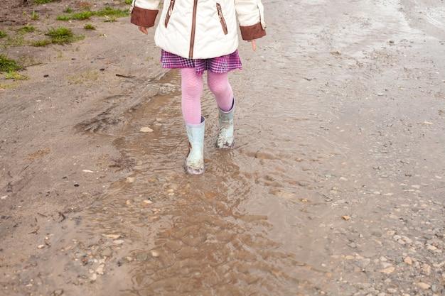 Une fille en collants roses et bottes en caoutchouc descend un ruisseau