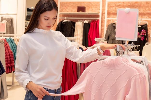 Fille commerçante. une belle fille aux longs cheveux noirs est dans une boutique de vêtements, choisit un pull pour elle-même. regarde les étiquettes de prix et vérifie la qualité. fond