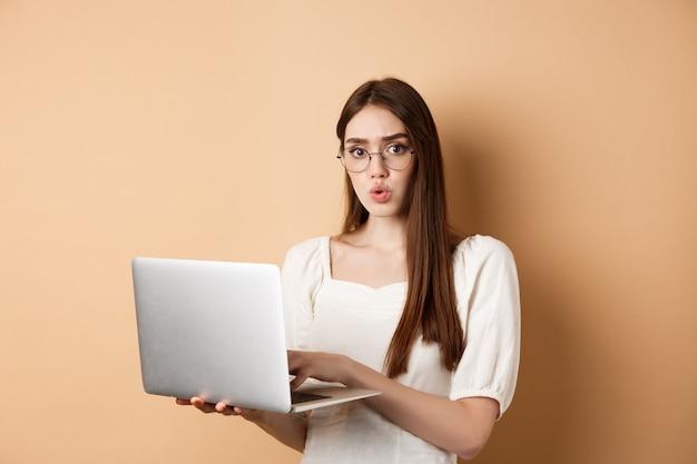 Fille concernée à lunettes regarde la caméra confuse, travaillant sur un ordinateur portable, ayant des problèmes avec l'ordinateur, debout sur fond beige.