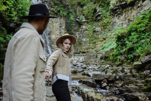 Fille conduit son petit ami à une belle cascade. la nature