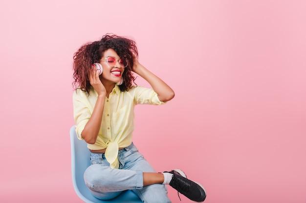 Fille confiante en baskets noires assis sur une chaise et écouter de la musique. femme frisée mulâtre heureuse en jeans vintage tenant des écouteurs avec les yeux fermés.
