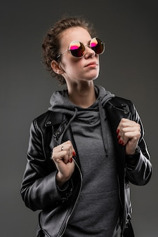 Fille confiante avec des traits du visage rugueux dans une veste noire isolée sur mur noir