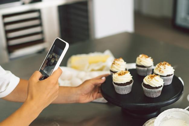 Fille de confiseur photographiant un petit gâteau pour sa fille de blog fait une photo de petits gâteaux sur un smartphone