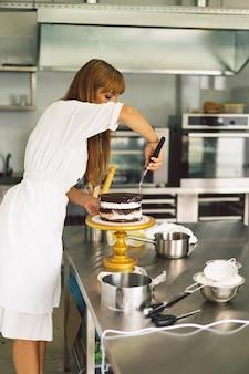 La fille de confiseur prépare un biscuit de gâteau avec de la crème blanche et des gâteaux de cuisson au chocolat