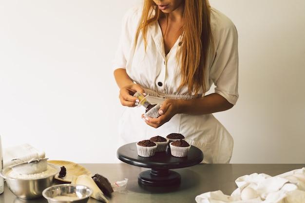 Une fille de confiseur prépare des ingrédients de concept de cupcakes pour la cuisson de produits à base de farine ou de desserts