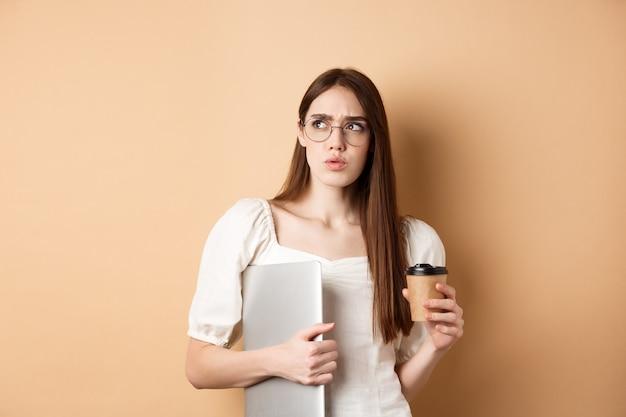 Fille confuse et pensive avec ordinateur portable à côté suspect, boire du café à emporter, debout contre beige.