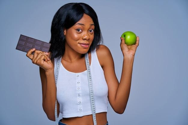 Fille confuse avec un ruban à mesurer sur son cou tenant une barre de chocolat noir et une pomme verte dans les mains. concept de régime