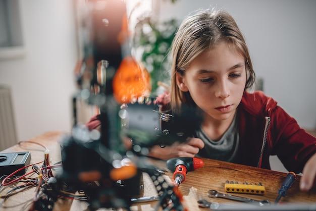 Fille construisant un robot à la maison