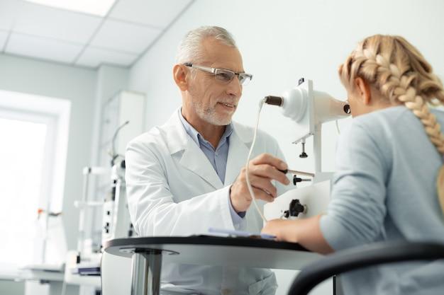 Fille consultante. ophtalmologue aux cheveux gris portant des lunettes et une fille de conseil en uniforme blanc