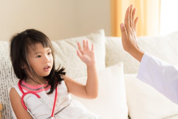 Fille en consultation chez le pédiatre. une fille sourit et donne cinq dollars au médecin.