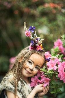 Fille de conte de fées. portrait d'une petite fille en robe de cerf avec un visage peint dans la forêt