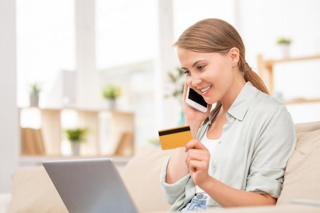 Fille contemporaine avec carte en plastique et smartphone parlant au directeur de la boutique en ligne en face de l'ordinateur portable