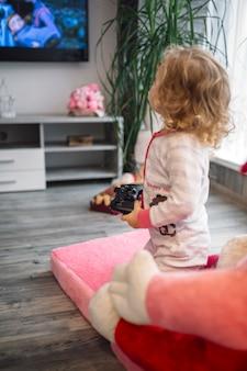 Fille avec contrôleur regardant la télévision