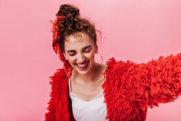 Fille cool en manteau rouge et t-shirt blanc riant sur rose