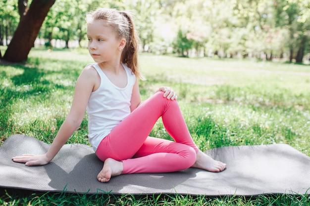 Fille cool en pantalon rose est assis sur carimate dans le parc