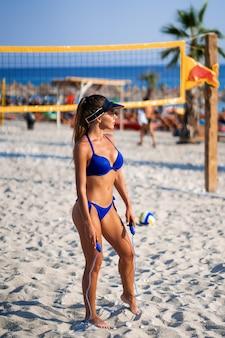 Fille avec corde à sauter à la plage. athlétique femme heureuse en maillot de bain sexy bleu à la mode, profitant du soleil exerçant mode de vie sain. formes parfaites du corps de remise en forme.