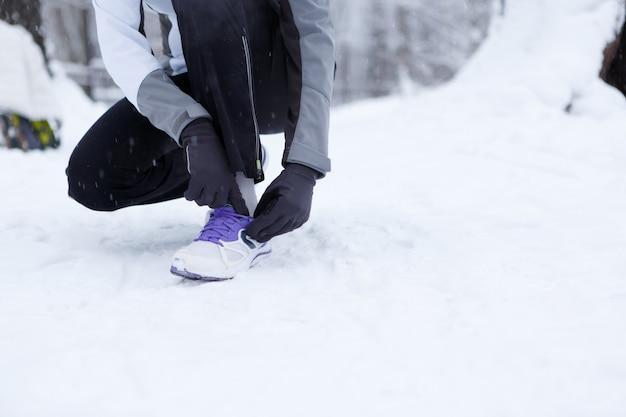 La fille corrige des chaussures en hiver