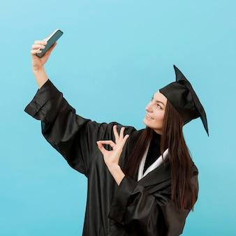 Fille en costume académique prenant selfie