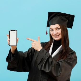 Fille en costume académique avec smartphone