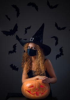 Une fille en costume de carnaval et portant un masque médical tient jack o lantern dans ses mains pour halloween