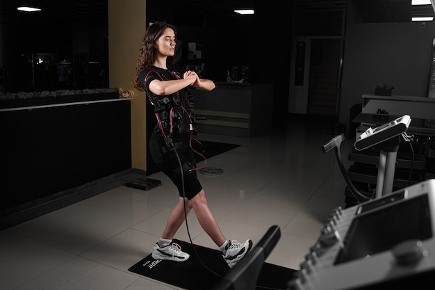 Fille en costume ems dans la salle de gym. entraînement sportif en combinaison de stimulation musculaire électrique. faire des exercices physiques.