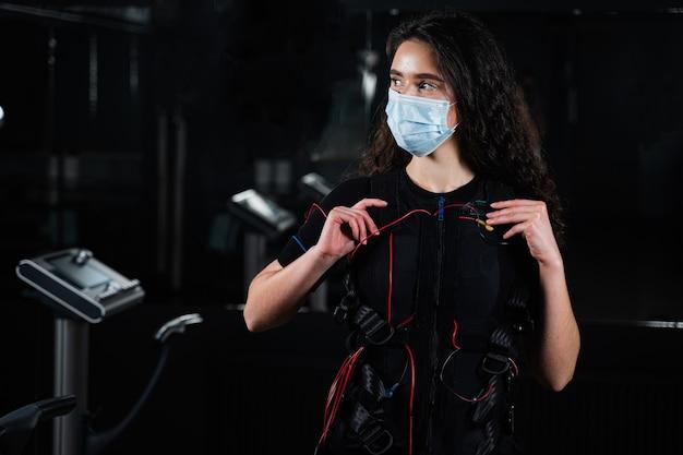 Fille en costume ems et masque médical dans la salle de gym. protection contre le coronavirus covid-19. entraînement sportif en combinaison de stimulation musculaire électrique.