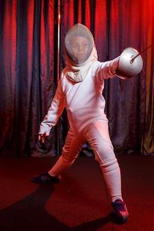 Fille en costume d'escrime avec une épée à la main, néon. un jeune modèle s'entraîne et s'entraîne en mouvement, en action. sports, jeunesse, mode de vie sain.