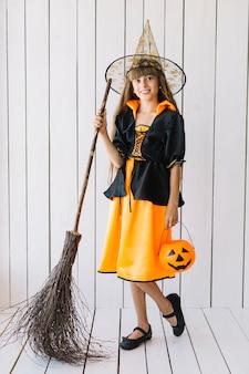 Fille en costume d'halloween avec panier et balai qui pose en studio