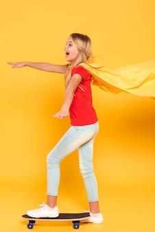 Fille avec costume de héros sur planche à roulettes