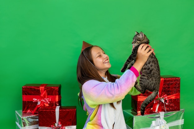 Fille en costume de licorne avec des coffrets cadeaux et jouant avec un chat