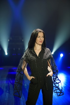 Fille en costume noir sur scène avec un fond bleu clair