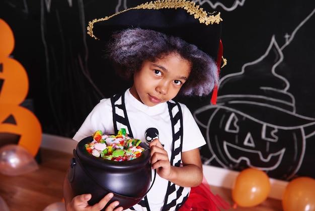 Fille en costume de pirate tenant un bol de bonbons