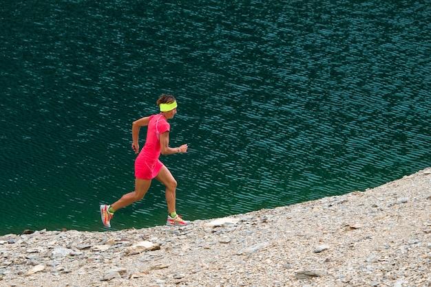 Fille avec costume rose court près d'un lac