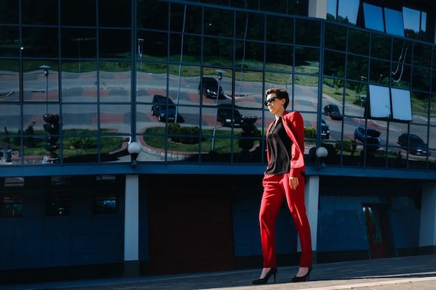 Une fille en costume rouge se dresse dans le contexte d'un bâtiment moderne de la ville