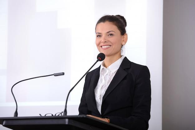 Une fille en costume se tient près du microphone et dit.