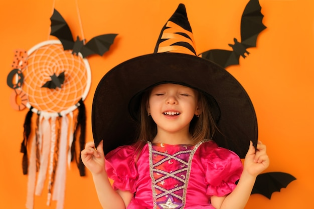 Une fille en costume de sorcière sur fond orange avec des chauves-souris tient un chapeau en fermant les yeux rêveusement