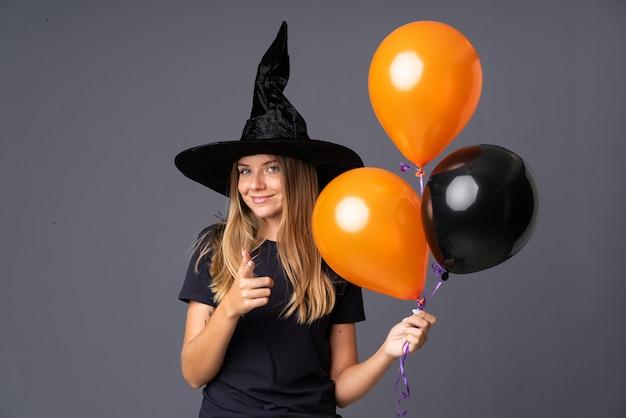 Fille avec costume de sorcière pour la fête d'halloween et pointant vers l'avant