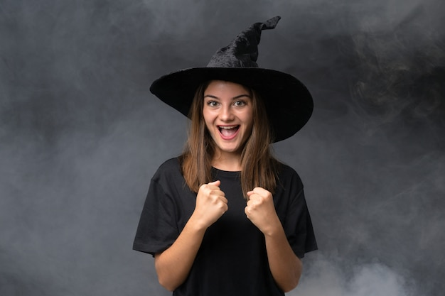 Fille avec costume de sorcière pour les fêtes d'halloween sur un mur noir isolé célébrant une victoire