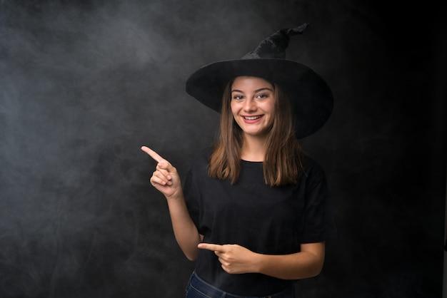 Fille avec costume de sorcière pour les fêtes d'halloween sur un mur noir isolé, pointant le doigt sur le côté