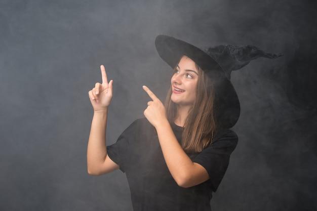 Fille avec costume de sorcière pour les fêtes d'halloween sur mur noir isolé pointant avec l'index une excellente idée