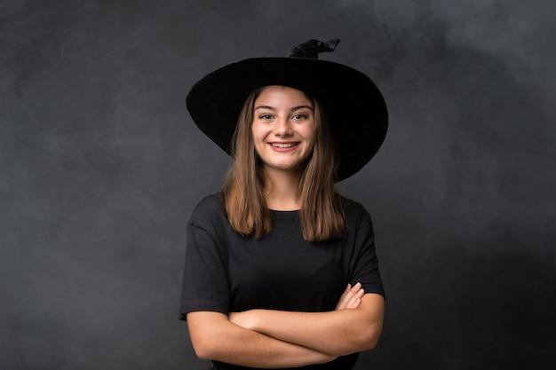 Fille avec costume de sorcière pour les fêtes d'halloween sur mur noir isolé en riant