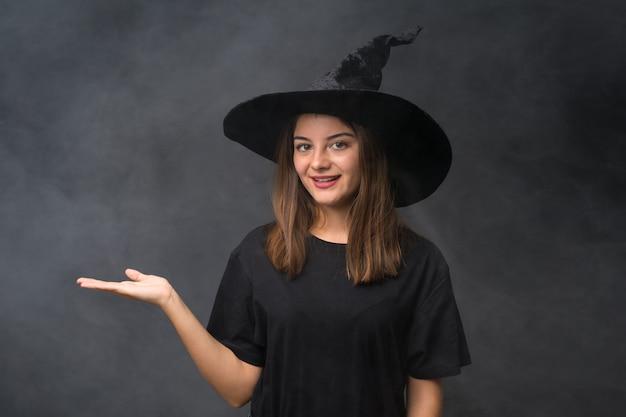 Fille avec costume de sorcière pour les fêtes d'halloween sur mur noir isolé tenant une surface imaginaire sur la paume